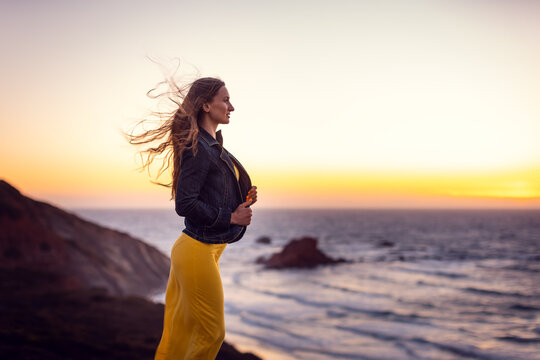 Woman on a sunset beach with the wind in her hair