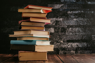 Stack of books in the colored cover lay on the wood table  with dark backround. Education learning...