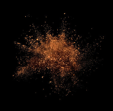 Cocoa powder explosion on black background