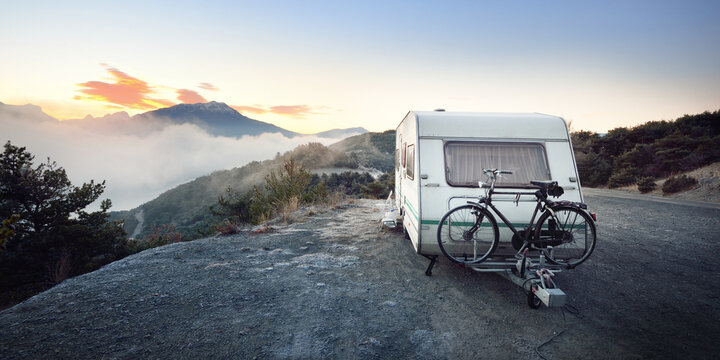 Caravan trailer with a bicycle near mountain lake Lac de serre-poncon in French Alps at sunrise. Golden sunlight, fog. Wanderlust, tourism, landmark, vacations in France. Transportation, RV, lifestyle