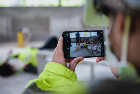 Smartphone shooting and record for report about work accidents and Unconscious of worker in workplace at construction site area while having the Medical assistance first aid team with equipment.