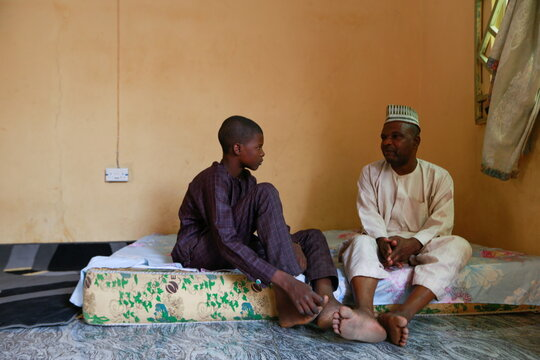 Balarabe Kagara speaks with one of his sons as the family awaits news of the release of two of his daughters after bandits kidnapped them from the JSS Jangebe school, in Zamfara