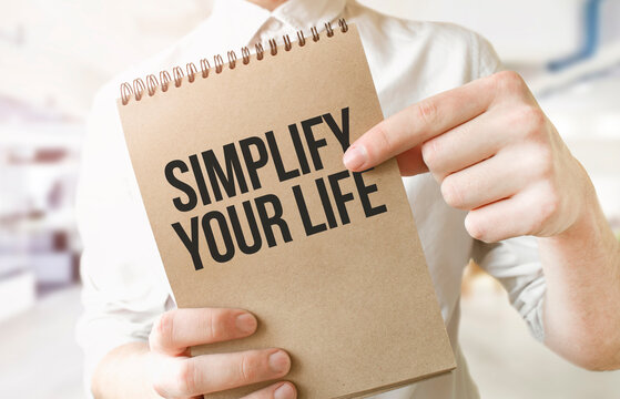 Text SIMPLIFY YOUR LIFE on brown paper notepad in businessman hands in office. Business concept