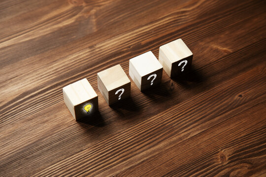wooden cubes with question mark symbol and light bulb icon