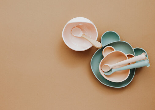 Flat lay composition with baby food accessory, plastic fruits, on light background. First baby food concept