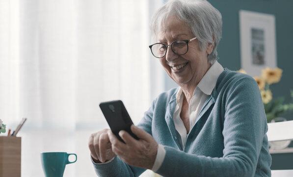 Smiling senior lady using her smartphone