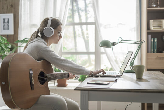 Woman playing guitar and connecting with her laptop