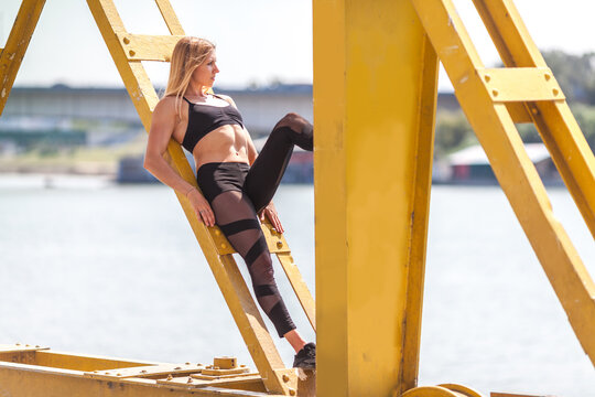 fit and muscular young woman standing on an old crane