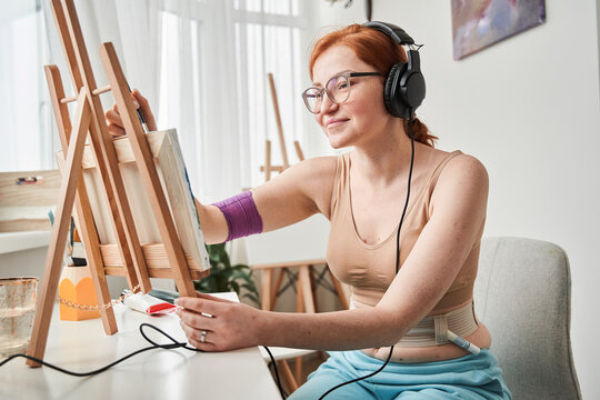 Woman painting in her living room