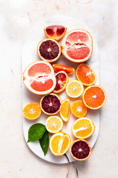 Flat lay citrus fruits with cut up lemons, grapefruits, oranges, blood oranges, and lemons on a cutting board.