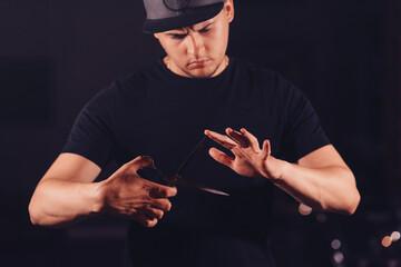 Obraz a man barber in a baseball cap holds sharp scissors in his hands - fototapety do salonu