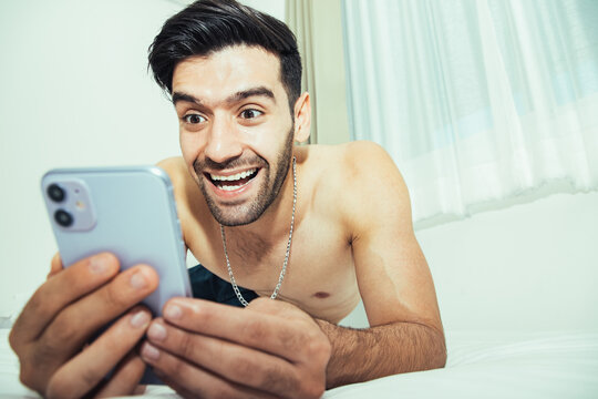 Handsome shirtless man on bed with intense face expression using mobile phone watching online porn enjoying alone in internet addiction after wake up.