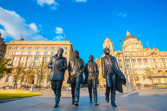 Liverpool, UK - May 17 2018: Bronze statue of the  Beatles stands at the Pier Head on the side of River Mersey, sculpted by Andrew Edwards and erected in December 2015