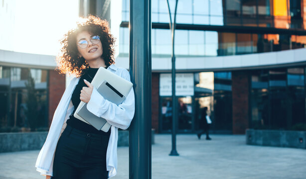 Caucasian businesswoman with curly hair and eyeglasses posing outside with a laptop