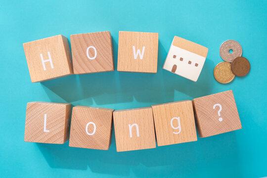 住宅ローンは何年?|「How long?」と書かれた積み木ブロックとおもちゃの家と小銭