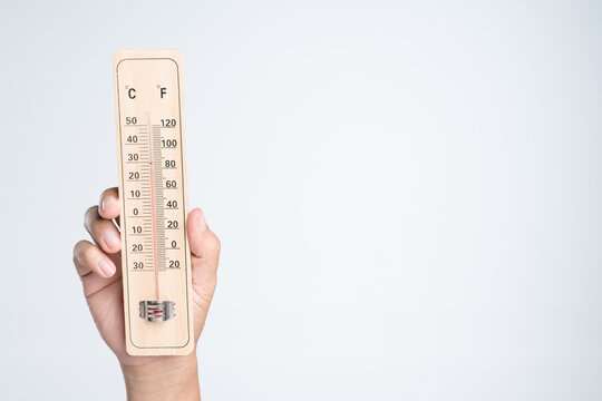 Hand holding classic thermometer for checking temperature