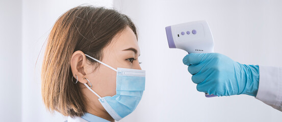 Hand of doctor use Temperature meter measure the forehead young woman.