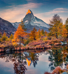 Beautiful autumn scenery. Astonishing sunrise on Grindjisee lake, Swiss Alps, Zermatt resort location, Switzerland, Europe. Incredible autumn view of Matterhorn peak reflected in calm lake waters.