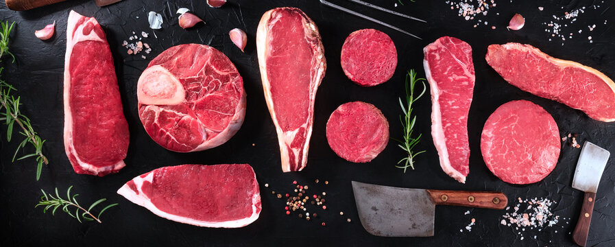 Meat cuts panorama. Raw beef pieces, shot from the top with herbs and seasoning, on a black background