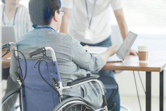 オフィスで働く車椅子の男性