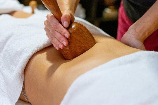 Masseuse giving a wood massage therapy massage to a client