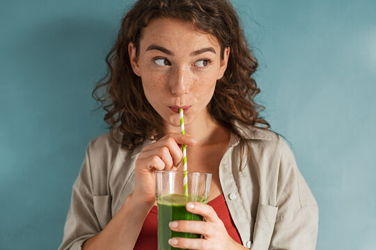Young woman drinking detox juice with straw on blue wall