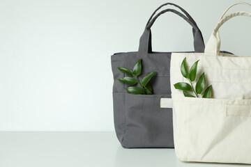 Fototapeta Stylish eco bags with twigs on white background obraz