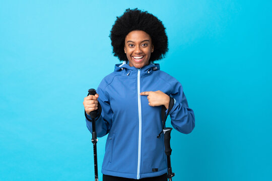 Young Africa American with backpack and trekking poles isolated on blue background with surprise facial expression