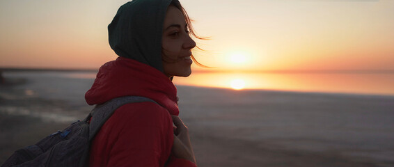 Obraz close up portrait woman traveler looking at sunrise at sea beach. girl in red jacket and hoodie with wind blowing golden hair from sunlight is enjoying scenery landscape - fototapety do salonu