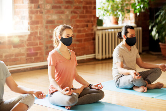 fitness, yoga and healthy lifestyle concept - group of people in black reusable masks meditating at studio
