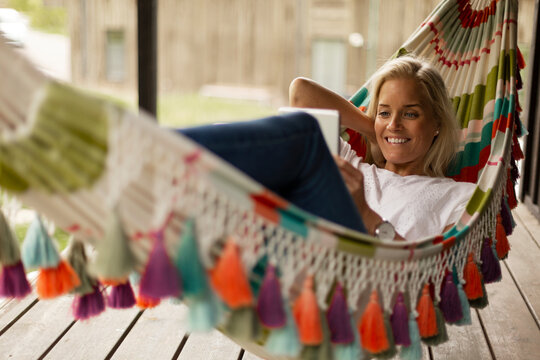 Woman lying in hammock and using tablet
