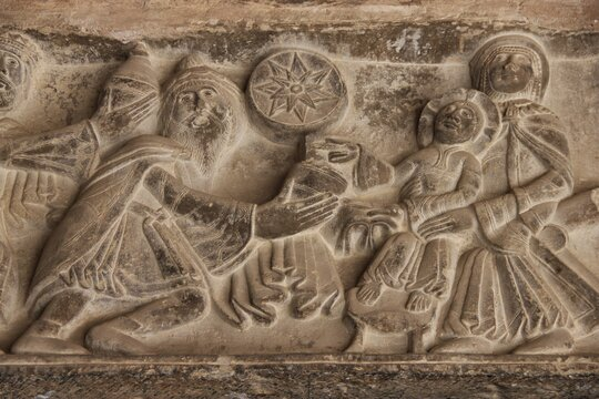 A nearly naive Romanesque relief in dark grey stone depicting the Adoration of the Magi at Huesca Cathedral, Spain