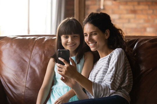 Smiling small Hispanic girl child and young mother look at cellphone screen speak on video call. Happy Latino mother and little daughter have webcam digital talk on smartphone. Virtual event concept.