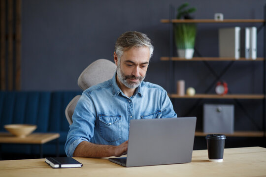 Grey-haired senior man working in home office with laptop. Business portrait of handsome manager sitting at workplace. Studying online, online courses. Business concept.