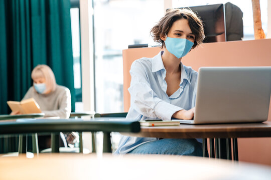 Happy caucasian girl in protective mask working with laptop at cafe