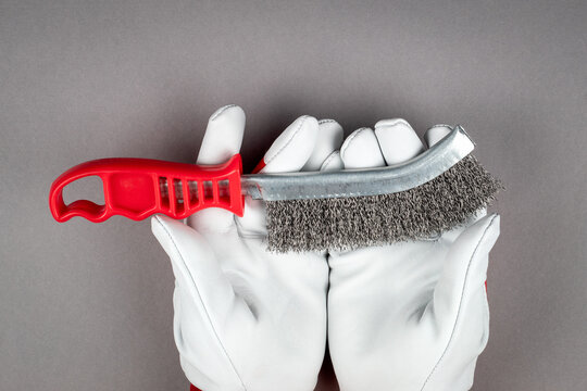 Metal wire brush with red plastic handle in a man's hand. White work leather gloves