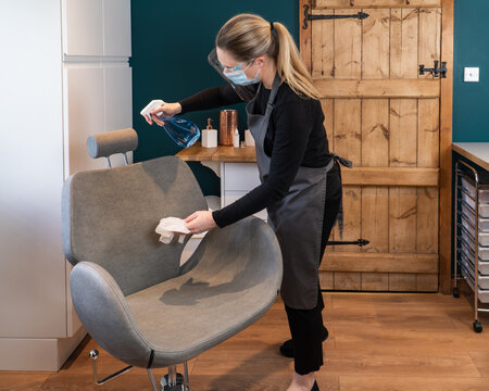 A female beauty therapist disinfectants and cleans a threading beauty chair in a salon in between clients. Woman wearing PPE during corona virus pandemic at work in a beauty salon.