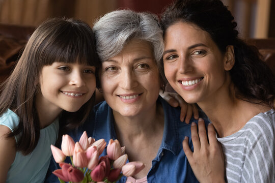 Close up family portrait of happy three generations of Hispanic women pose together celebrating anniversary. Smiling adult female with little daughter and mature grandmother on woman day.