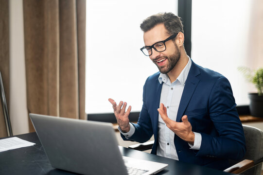 Young bearded businessman entrepreneur in business wear explaining himself, discussing project, gesturing, presenting new business idea to client, team or to investor online on video call via laptop