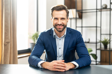 Fototapeta Young bearded confident successful man in business casual clothes looking at camera, skilled job applicant is ready for an online interview on a video call, sitting at the desk, holding hands together
