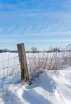 An old rustic wooden fence post in a snowy scenic landscape with copy space for your text