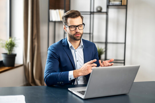 Young bearded entrepreneur, business coach in formal wear having coaching session on leadership and sales or discussing project, gesturing, presenting strategy, idea online on video call via laptop