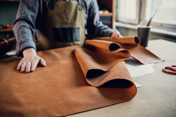 A young apprentice in a boot workshop prepares leather for further use on a large table. - fototapety na wymiar