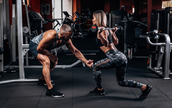 man personal trainer and woman with barbell flexing muscles in gym