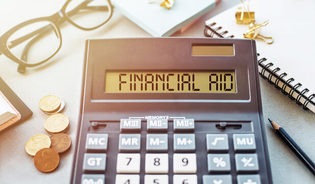 Word FINANCIAL AID written on calculator on office table.