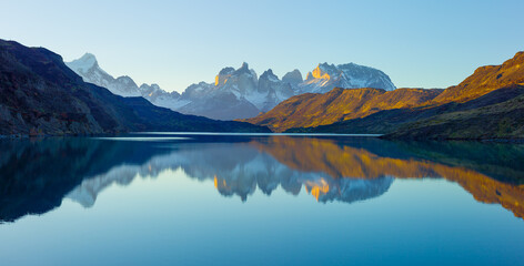 Panoramic view of a landscape with the Paine mountain range reflecting in the Serrano river at sunset