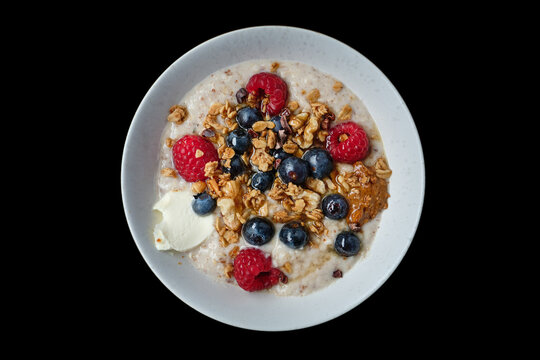 Top view of healthy cereal and oatmeal breakfast with berries and nuts in a white bowl. Ideal for those suffering from Irritable bowel syndrome or Small intestinal bacterial overgrowth. Isolated.