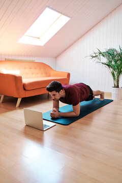 Man following exercise class on laptop