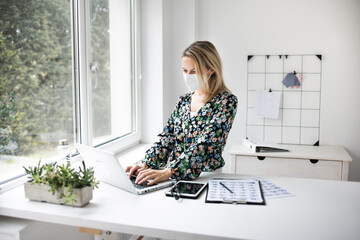 Fototapeta Businesswoman with ffp2 mask working at standing workstation in office