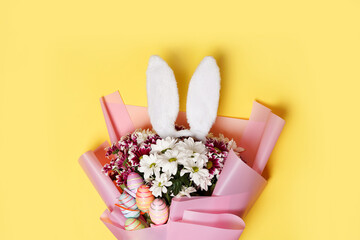Easter bunny ears, spring flowers and colorful eggs on yellow background